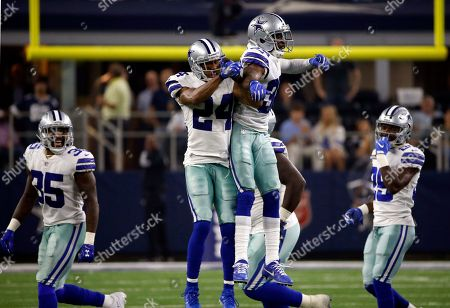 Dallas Cowboys cornerback Nolan Carroll II (24) and cornerback Anthony Brown (30) celebrate an interception by Brown in the second half of an NFL football game against the New York Giants, in Arlington, Texas