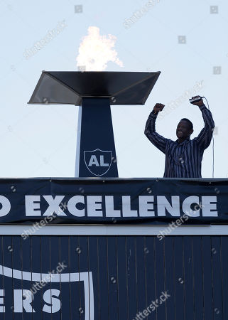 Former Oakland Athletic and Baseball Hall of Fame inductee Rickey Henderson gestures after lighting a ceremonial torch for former Oakland Raiders owner Al Davis before an NFL football game between the Oakland Raiders and the New York Jets in Oakland, Calif