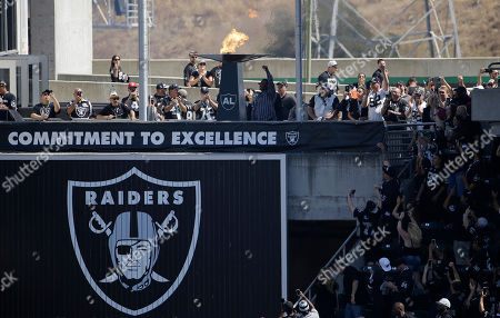 Former Oakland Athletic and Baseball Hall of Fame inductee Rickey Henderson waves after lighting a ceremonial torch for former Oakland Raiders owner Al Davis before an NFL football game between the Oakland Raiders and the New York Jets in Oakland, Calif