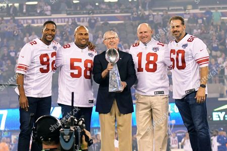 Former New York Giants players Michael Strahan, (92), Antonio Pierce (58), left, and Jeff Feagles (18), right, and Shaun O'Hara, (60) watch as Tom Coughlin, center, holds the Super Bowl trophy during a halftime ceremony of an NFL football game between the New York Giants and the Detroit Lions, in East Rutherford, N.J