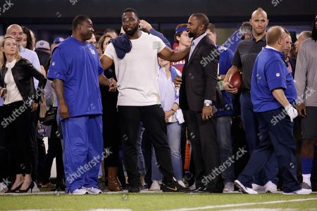 Former New York Giants player Justin Tuck talks to friends before an NFL football game against the Detroit Lions, in East Rutherford, N.J