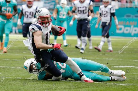 Miami Dolphins linebacker Spencer Paysinger (42) tackles New England Patriots wide receiver Julian Edelman (11), during the first half of an NFL football game, in Miami Gardens, Fla