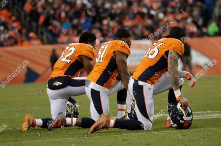 From left, Denver Broncos' Corey Nelson, Todd Davis, and Shane Ray kneel as Broncos linebacker Zaire Anderson is tended to on the field after an injury in the second half of an NFL football game against the Oakland Raiders, in Denver