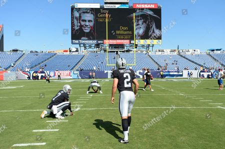 A video board tribute to country music singers Don Williams and Troy Gentry is displayed as Oakland Raiders kicker Giorgio Tavecchio (2) warms up before an NFL football game against the Tennessee Titans, in Nashville, Tenn. Both singers died Friday, Sept. 8
