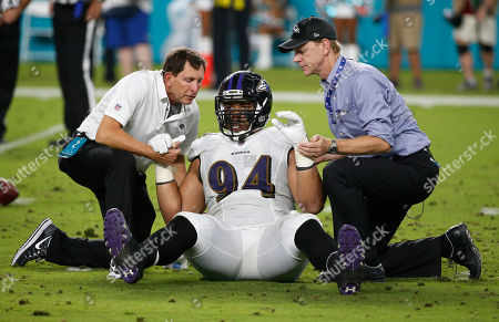 Baltimore Ravens defensive end Carl Davis (94) is helped to his feet, during the second half of an NFL preseason football game against the Miami Dolphins, in Miami Gardens, Fla
