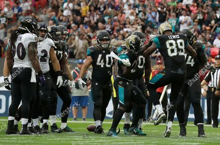 Jacksonville Jaguars running back Leonard Fournette (27) indulges in a celebration routine with Marcedes Lewis (89) after scoring a touchdown against the Baltimore Ravens during the second half of an NFL football game at Wembley Stadium in London