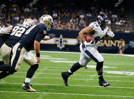 Baltimore Ravens defensive end Carl Davis (94) runs after intercepting a pass, during the first half of an NFL preseason football game against the New Orleans Saints, in New Orleans