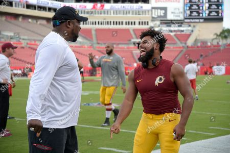Former Tampa Bay Buccaneers defensive lineman Warren Sapp shares a laugh with Washington Redskins linebacker Nico Marley, right, during warmups before an NFL preseason football game, in Tampa, Fla
