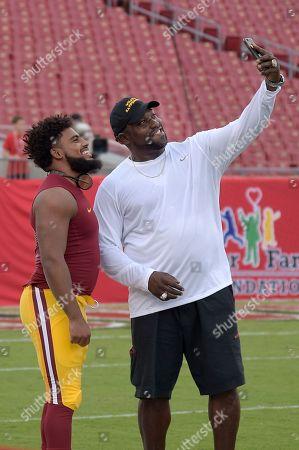 Former Tampa Bay Buccaneers defensive lineman Warren Sapp, right, makes a selfie photo with Washington Redskins linebacker Nico Marley during warmups before an NFL preseason football game, in Tampa, Fla