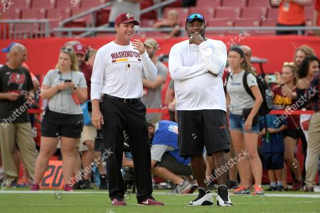 Washington Redskins head coach Jay Gruden watches warmups with former Tampa Bay Buccaneers defensive tackle Warren Sapp on the field before an NFL preseason football game, in Tampa, Fla