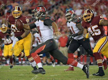 Tampa Bay Buccaneers quarterback Sefo Liufau (8) runs away from Washington Redskins defensive tackle A.J. Francis (69) and linebacker Pete Robertson (45) during the second quarter of an NFL preseason football game, in Tampa, Fla