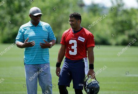 Russell Wilson, Warren Moon. Seattle Seahawks quarterback Russell Wilson, right, walks off the field with Seahawks former quarterback Warren Moon following NFL football practice, in Renton, Wash