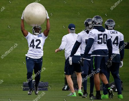 Seattle Seahawks linebacker Arthur Brown (42) lifts an inflatable ball during NFL football practice, in Renton, Wash