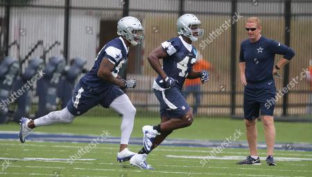 Dallas Cowboys coach Jason Garrett, right, watches defensive end Taco Charlton (97) and line backer Joseph Jones (43) during an NFL football rookie minicamp in Frisco, Texas