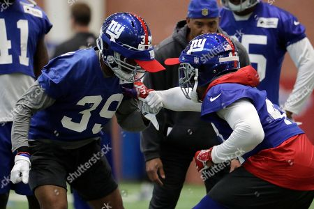 New York Giants' Michael Hunter Jr., left, and Valentino Blake run a drill during the team's organized team activities at its NFL football training facility, in East Rutherford, N.J