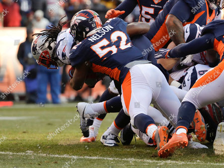 New England Patriots running back LeGarrette Blount scores past Denver Broncos inside linebacker Corey Nelson during the first half of an NFL football game, in Denver