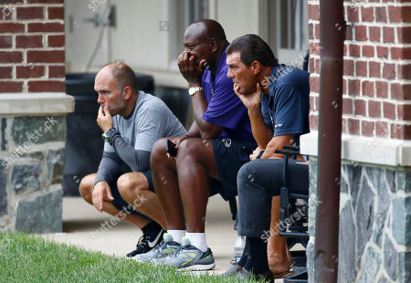 Baltimore Ravens assistant general manager Eric DeCosta, from left, general manager and executive vice president Ozzie Newsome and owner Stephen Bisciotti look out at practice fields at the end of an NFL football training camp practice in Owings Mills, Md