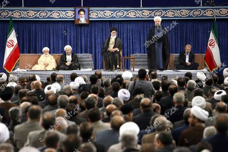 In this picture released by official website of the office of the Iranian supreme leader, President Hassan Rouhani, speaks during his official endorsement ceremony as Supreme Leader Ayatollah Ali Khamenei, center, parliament speaker Ali Larijani, right, judiciary chief Sadeq Larijani, second left, and head of the Assembly of Experts and secretary of Guardian Council Ahmad Jannati listen in Tehran, Iran