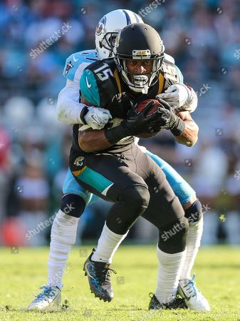 Jacksonville Jaguars wide receiver Allen Robinson after a catch for a first down is tackled by Tennessee Titans defensive back Valentino Blake during the second half of an NFL football game, in Jacksonville, Fla