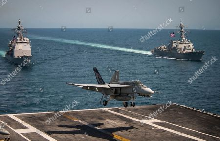 "In this image released by the U.S. Navy, an F/A-18E Super Hornet from the ""Kestrels"" of Strike Fighter Squadron (VFA) 137 lands on the flight deck of the Nimitz-class aircraft carrier USS Carl Vinson, as the guided-missile cruiser USS Lake Champlain, left, and guided-missile destroyer USS Wayne E. Meyer trail behind as they transit the western Pacific Ocean"