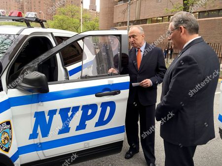 In this May 10, 2016 photo provided by the New York City Police Department, NYPD Commissioner William Bratton, second from right, examines a bullet resistant safety shield affixed to the side window of an NYPD patrol car in New York. After two officers were fatally gunned down through the window of their squad car in 2014, the city embarked on plan to outfit all of its squad cars with inch-thick bullet-resistant glass and armored door panels. That plan did not cover RV-like mobile command posts, like the one Officer Miosotis Familia sat inside when she was fatally shot while on duty in the early hours of