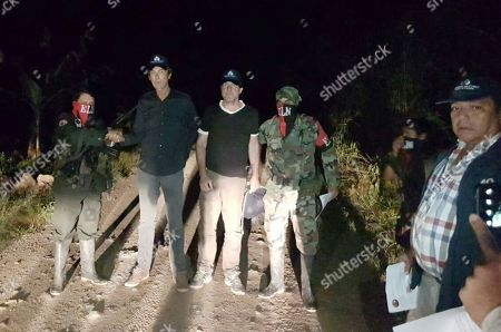 In this photo released by Colombia's Ombudsman Press Office, rebels of Colombia's National Liberation Army, ELN, release Dutch journalists Derk Bolt, second from left, and Eugenio Follender, second from right, north of Santander, Colombia, . The two Dutch journalists, who were held captive for almost a week by the leftist rebels in Colombia, were released unharmed, Dutch Foreign Affairs Minister Bert Koenders said early Saturday