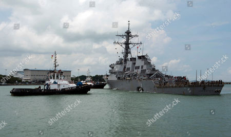 In this, photo provided by the U.S. Navy, tugboats from Singapore assist the Guided-missile destroyer USS John S. McCain (DDG 56) as it steers towards Changi Naval Base, Singapore following a collision with the merchant vessel east of the Straits of Malacca and Singapore. The collision between the USS John S. McCain and an oil tanker has exposed a long-simmering dispute between Singapore and Malaysia over which country should control a 60-meter wide guano-encrusted outcropping at the edge of the South China Sea. Malaysia and Singapore both say the accident happened in their territorial waters because of the competing claims to Pedra Branca