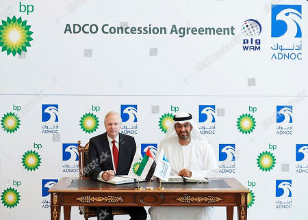 In this picture provided by WAM the state-run news agency of the United Arab Emirates, Sultan Ahmed Al Jaber, right, ADNOC Group Chief Executive Officer, and member of the Supreme Petroleum Council of the Emirate of Abu Dhabi, and Bob Dudley, BP Group Chief Executive, pose for a picture following a deal in Abu Dhabi, . Oil giant BP PLC has agreed to an onshore oil deal with the Mideast emirate of Abu Dhabi worth $2.22 billion following years of negotiations