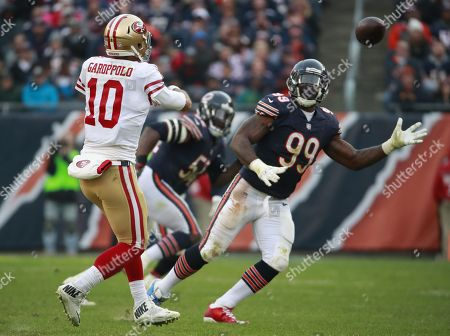 Jimmy Garoppolo, Lamarr Houston. San Francisco 49ers quarterback Jimmy Garoppolo (10) throws a pass as Chicago Bears linebacker Lamarr Houston (99) pressures during an NFL football game, in Chicago. The 49ers won the game 15-14