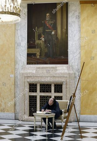 A Romanian man writes into the condolences book, backed by the portrait of Carol I of Romania , the founder of the Romanian Monarchy, in memory of former King Michael I of Romania inside the Royal Palace (now National Arts Museum), in Bucharest, Romania, 06 December 2017. The royal house of Romania announced on 05 December 2017 that former King Michael I of Romania has died at his residence in Switzerland at the age of 96. King Michael I of Romania was forced to abdicate by the communists in 1947.