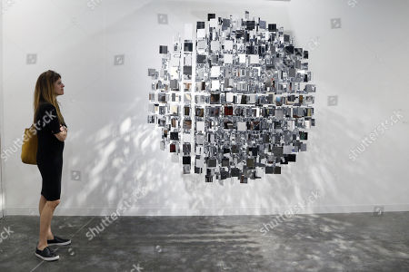 An Art Basel patron looks at 'Sphere Miroir' artwork by Argentinian artist Julio Le Parc during Art Basel in Miami, Florida, USA, 06 December 2017. Art Basel represents over 250 art galleries onsite at the Miami Beach Convention Center and is considered one of the world's largest art festivals with art events throughout the city.