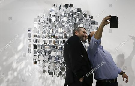 Art Basel patrons take a photo with their cell phones in front of 'Sphere Miroir' artwork by Argentinian artist Julio Le Parc during Art Basel in Miami, Florida, USA, 06 December 2017. Art Basel represents over 250 art galleries onsite at the Miami Beach Convention Center and is considered one of the world's largest art festivals with art events throughout the city.