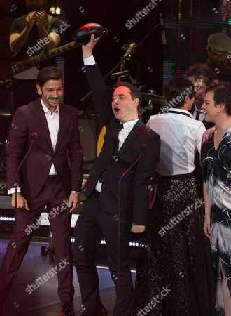 """Chile's producer Juan de Dios Larrain accept the award for Best Fiction Film """"Una Mujer Fantastica"""" during the Fenix Iberoamerican Film Awards at Esperanza Iris Theater in Mexico City, . At left is Mexican actor Diego Luna, and at right is Chile's actor Daniela Vega"""