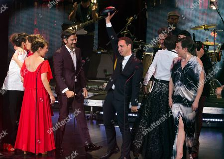 """Chile's producer Juan de Dios Larrain accepts the award for Best Fiction Film """"Una Mujer Fantastica"""" during the Fenix Iberoamerican Film Awards at Esperanza Iris Theater in Mexico City, . Fourth from left is Mexican actor Diego Luna, and at far right is Chile's actor Daniela Vega"""