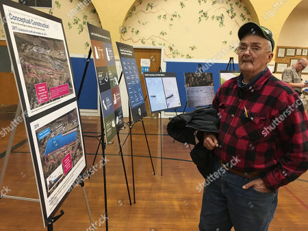 Tom Kelly of Paradise, Calif., looks at charts and photos at a town hall meeting, in Oroville, Calif. Department of Water Resources officials heard an earful from residents concerned about efforts to rebuild spillways at Oroville Dam, which were severely damaged in February, prompting nearly 200,000 to evacuate