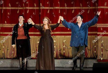 """Russian soprano Anna Netrebko, center, Azerbaijani tenor Yusif Eyvazov, right, and Italian baritone Luca Salsi acknowledge the applause of the audience at the end of La Scala opera house's gala season opener, Umberto Giordano's opera """"Andrea Chernier"""", at the Milan La Scala theater, Italy, . The season-opener Thursday, held each year on the Milan feast day St. Ambrose, is considered one of the highlights of the European cultural calendar"""