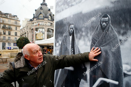 "French photographer and director Raymond Depardon unveils an exhibition of his Olympics Games photos as part of Reporters Sans Frontieres book for the liberty of the press, in front of Paris city hall, in Paris, France, . The exhibition entitled ""Les JO de Raymond Depardon"" presents his photos of the Olympic Games between 1964 and 1980. Caption of the picture at right : ""US Bob Beamon, right, protects from a rainstorm just after he breaks the world record in the long jump by nearly two feet during the 1968 Mexico City Olympic Games"