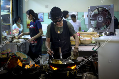 70-year-old chef Jay Fai (C) cooks on coal powered stoves at her Michelin star restaurant in Bangkok, Thailand, 08 December 2017. The Raan Jae Fai restaurant, run by Chef Jay Fai and popular both for Jay Fai's oversized glasses as well as its fried drunken noodles and crab omelette (1,000THB or 26 euro), was awarded on 07 December 2017 a Michelin star, making it the first street food restaurant in Thailand to be awarded a Michelin star.