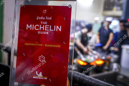 A waitress shows the framed award star from Michelin as 70-year-old chef Jay Fai (R) cooks on coal powered stoves at her Michelin star restaurant in Bangkok, Thailand, 08 December 2017. The Raan Jae Fai restaurant, run by Chef Jay Fai and popular both for Jay Fai's oversized glasses as well as its fried drunken noodles and crab omelette (1,000THB or 26 euro), was awarded on 07 December 2017 a Michelin star, making it the first street food restaurant in Thailand to be awarded a Michelin star.