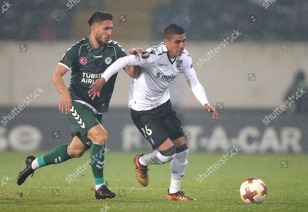 Stock Image of Konyaspor's Vedat Bora, left, vies for the ball with Vitoria's Paolo Hurtado during the Europa League group I soccer match between Vitoria SC and Konyaspor at the D. Afonso Henriques stadium in Guimaraes, Portugal