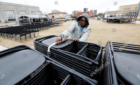 Stock Photo of Robert Ferguson, struggles to release a strap securing a platform of chairs beside the state's two newest museums, the Museum of Mississippi History and the Mississippi Civil Rights Museum, in Jackson, Miss. Ferguson and others have to arrange 2,500 seats in the small plaza that rests in front of the two museums. The long-planned Saturday ceremony will mark Mississippi's bicentennial of admission into the union, however the appearance of President Donald Trump at the ceremony has drawn the ire of U.S. Reps. John Lewis, D-Ga., and Bennie Thompson, D-Miss., who announced Thursday they won't attend the opening of Mississippi civil rights and history museums. What was intended as a moment of racial unity and atonement in the state with the largest share of African-Americans is descending into racial and partisan strife after Republican Mississippi Gov. Phil Bryant invited fellow Republican Trump to attend