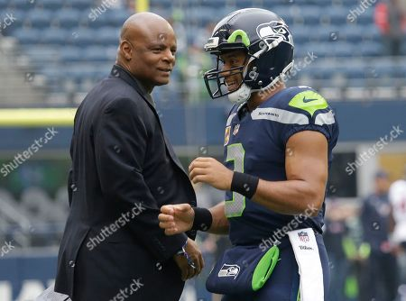 NFL Hall of Fame quarterback Warren Moon, left, stands on the field with Seattle Seahawks quarterback Russell Wilson, right, before an NFL football game between the Seahawks and the Houston Texans, in Seattle