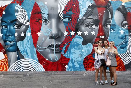 Stock Picture of Women take a photo in front of a building covered with a mural by American artist Tristan Eaton in the Wynwood district during Art Basel in Miami, Florida, USA, 07 December 2017.  Art galleries and artists from all over the world descend on Miami for the event which is considered one of the world's largest art festivals with art events throughout the city.