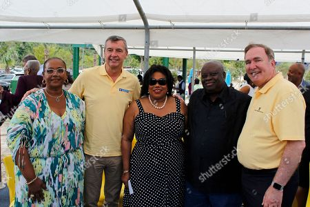Stock Photo of Richard D. Fain, Kenneth E. Mapp, Michael Bayley. Royal Caribbean Chairman & CEO, Richard D. Fain, right, U.S. Virgin Islands governor, Kenneth E. Mapp, U.S. Virgin Islands Commissioner, Beverly Nicholson-Doty, Royal Caribbean International President & CEO, Michael Bayley, and Magens Bay Authority Vice-Chairperson, Barbgara Petersen, pose for a photo with local residents during a ceremony at the Magen's Bay Beach, in St. Thomas, U.S. Virgin Islands