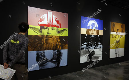 Stock Picture of Art Basel patron look at several pieces titled  'Exquisite Self Portrait' by American Artist Rob Pruitt during Art Basel in Miami, Florida, USA, 08 December 2017. Art galleries and artists from all over the world descend on Miami for the event which is considered one of the world's largest art festivals with art events throughout the city.