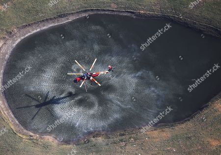 A water-dropping helicopter picks up water in a pond as the Lilac Fire burned near Bonsall in northern San Diego County