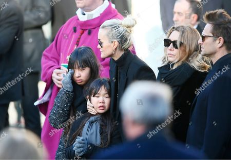 French rock star Johnny Hallyday's wife Laetitia, center, his daughters Jade, left, and Joy, Laura Smet and son David Hallyday, right, arrive at La Madeleine church for Johnnny Hallyday's funeral ceremony in Paris, Saturday, Dec.9, 2017. France is bidding farewell to its biggest rock star, honoring Johnny Hallyday with an exceptional funeral procession down the Champs-Elysees, a presidential speech and a motorcycle parade, all under intense security