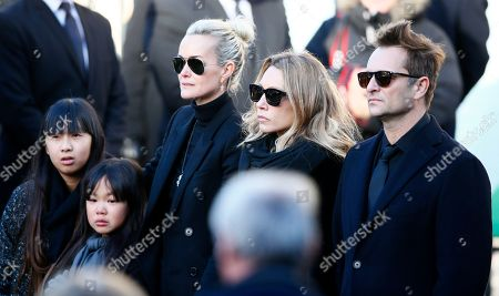 French rock star Johnny Hallyday's wife Laetitia, second left, his daughters Jade, left, and Joy, Laura Smet, second right, and son David Hallyday, right, arrive at La Madeleine church for Johnnny Hallyday's funeral ceremony in Paris, Saturday, Dec.9, 2017. France is bidding farewell to its biggest rock star, honoring Johnny Hallyday with an exceptional funeral procession down the Champs-Elysees, a presidential speech and a motorcycle parade, all under intense security