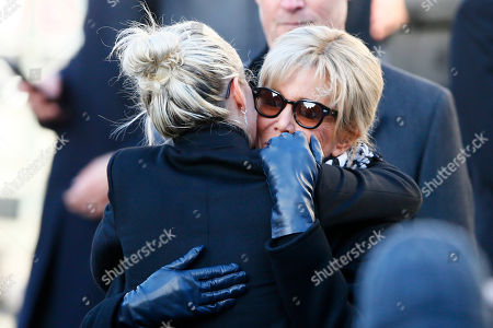 French President Emmanuel Macron's wife Brigitte, right, hugs French rock star Johnny Hallyday's widow Laetitia at La Madeleine church during Johnny Hallyday's funeral ceremony in Paris, Saturday, Dec.9, 2017. France is bidding farewell to its biggest rock star, honoring Johnny Hallyday with an exceptional funeral procession down the Champs-Elysees, a presidential speech and a motorcycle parade, all under intense security