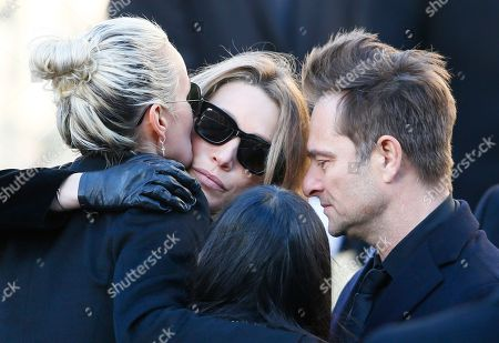 French rock star Johnny Hallyday's widow Laetitia, left, hugs Hallyday's daughter Laura Smet while his son David Hallyday react during Johnny Hallyday's funeral ceremony at La Madeleine church for Johnny Hallyday's funeral ceremony in Paris, Saturday, Dec.9, 2017. France is bidding farewell to its biggest rock star, honoring Johnny Hallyday with an exceptional funeral procession down the Champs-Elysees, a presidential speech and a motorcycle parade, all under intense security